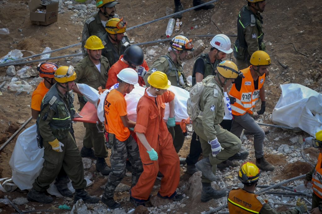 Rescue workers carry out a victim of the building collapse in Tel Aviv, Tuesday. (Flash90)