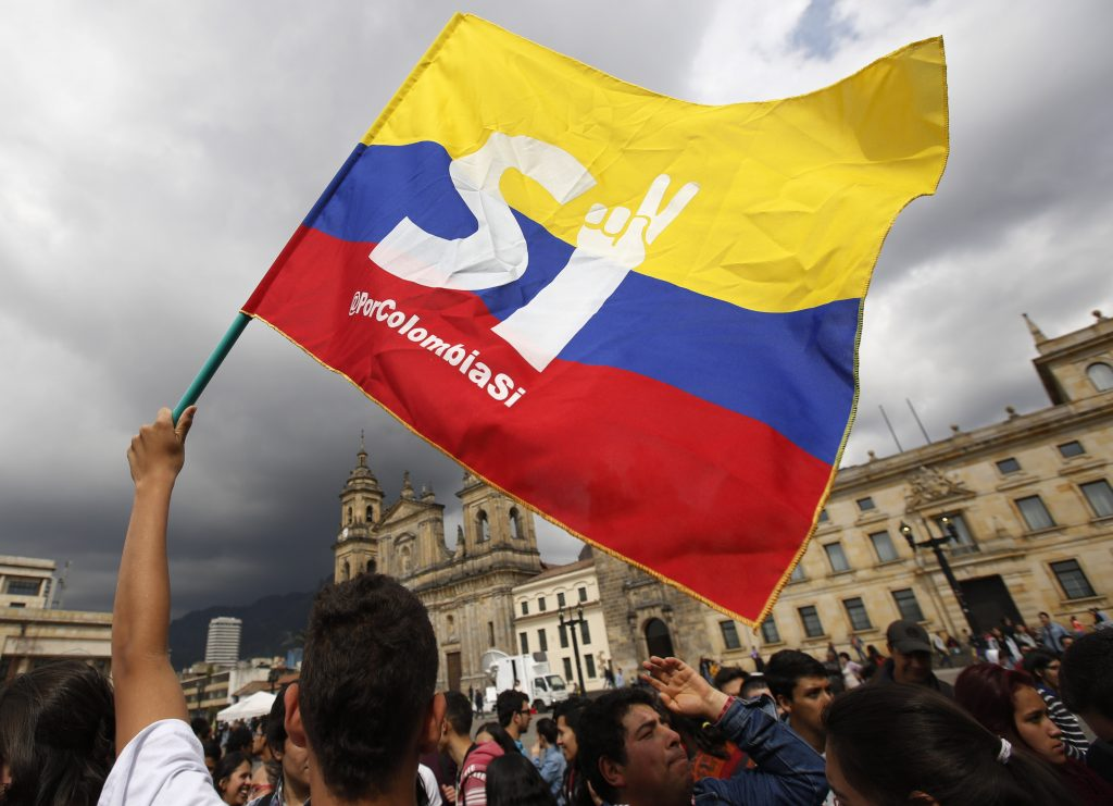 A supporter of the peace deal signed between the Colombian government and rebels of the Revolutionary Armed Forces of Colombia, FARC, wave a flag during a rally in front of Congress, in Bogota, Colombia, Monday. Colombians rejected a peace deal with leftist rebels of the Revolutionary Armed Forces of Colombia, FARC, by a razor-thin margin in a national referendum Sunday, dismissing years of negotiations and delivering a setback to President Juan Manuel Santos. (AP Photo/Fernando Vergara)