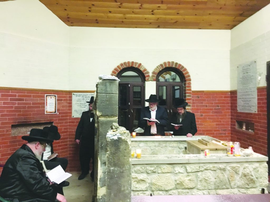 "Davening at the kever of Harav Shaya'le of Kerestir, zy""a. The Sulitzer Rebbe is sitting to the left, and Rabbi Pesach Lerner is standing at the center."