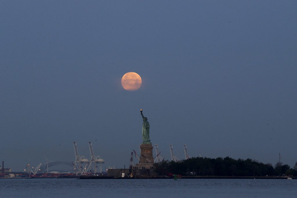 FILE - This Sunday, June 23, 2013 file photo shows a supermoon over the Statue of Liberty in New York. Monday, Nov. 14, 2016 will have the closest full moon of the year, or every 14 months to be precise. It will also be the closest the moon comes to us in almost 69 years. And it won't happen again for another 18 years. (AP Photo/Julio Cortez)