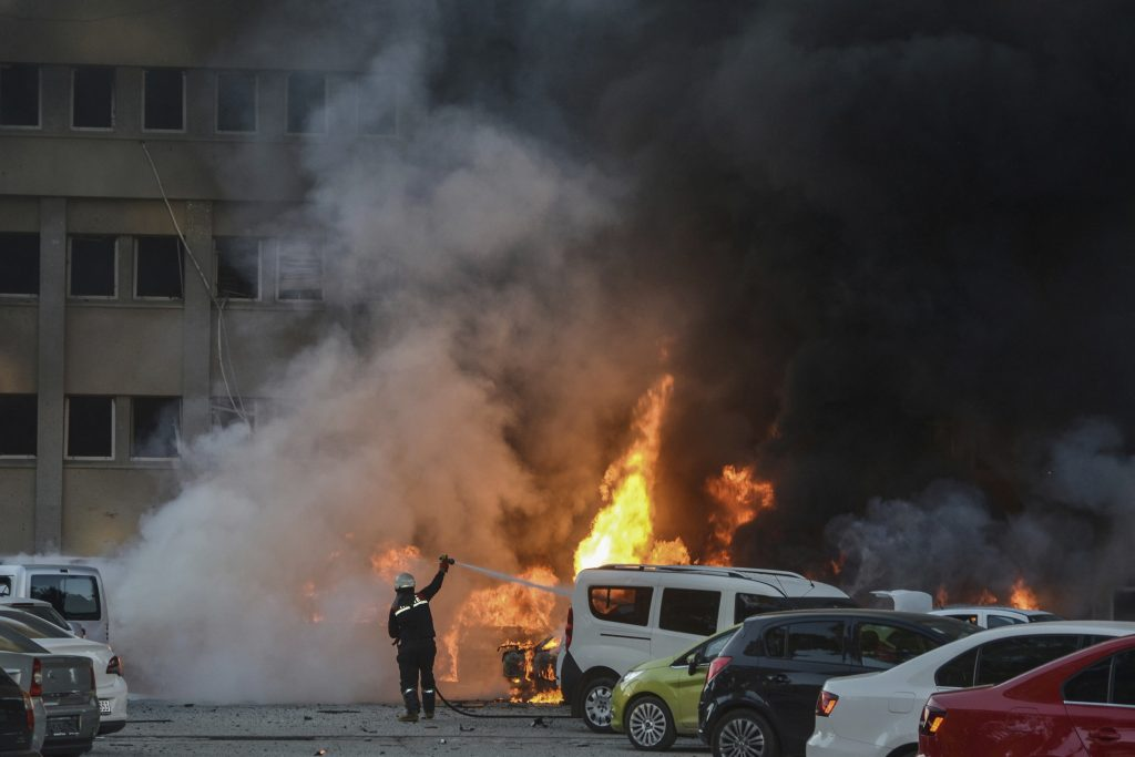 Firefighters work after an explosion in southern city of Adana, Turkey, Thursday, Nov. 24, 2016. The explosion occurred early Thursday in the parking lot of a government building, officials said. Turkish authorities imposed a media ban, barring broadcast and publication of graphic images or information that might hinder the investigation. (IHA via AP)