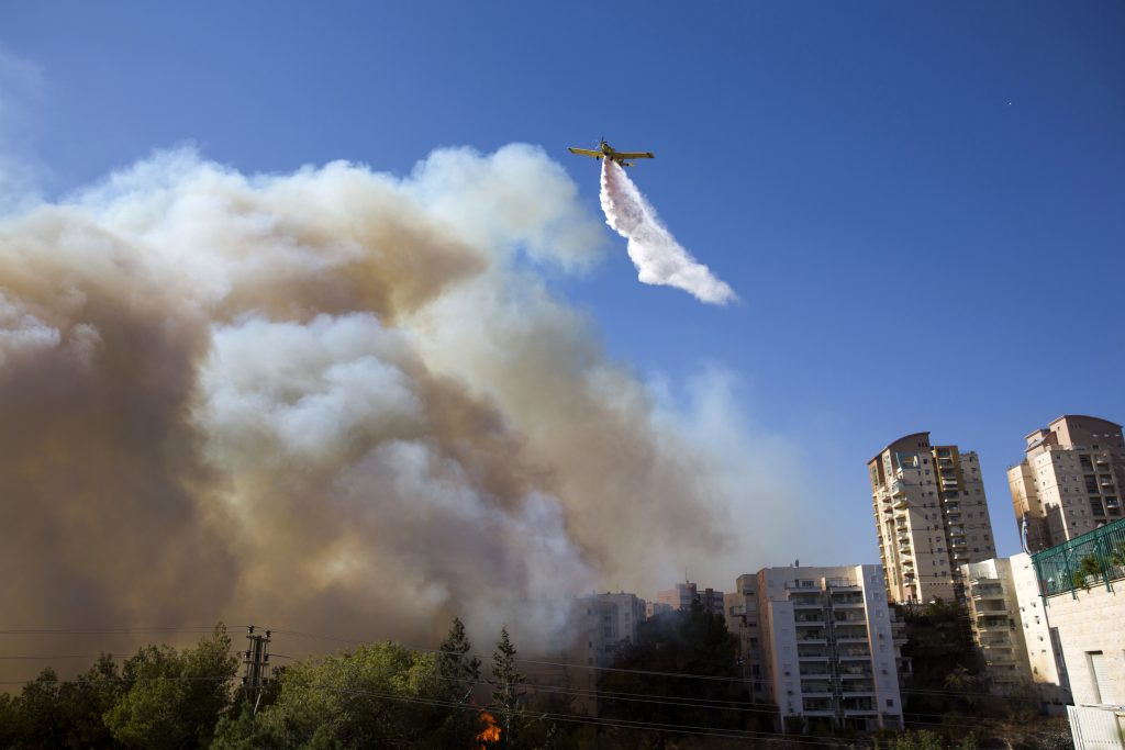 A plane flies over the wildfires in Haifa, Israel, Thursday, Nov. 24, 2016. Israeli police have arrested four Palestinians in connection with one of several large fires that damaged homes and prompted the evacuation of thousands of people in the past few days. Police are investigating the causes, including possible arson. Windy and hot weather have helped fan the flames. The blazes started three days ago near Jerusalem and in the north. Hundreds of homes were damaged. Russia, Italy and other countries are assisting the Israeli firefighters.(AP Photo/Ariel Schalit)