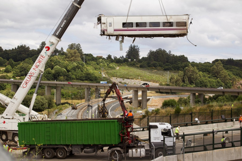 A derailed train car is lifted by a crane earlier in the week at the site of a train accident in Santiago de Compostela, Spain. (AP Photo/Lalo R, Villar)