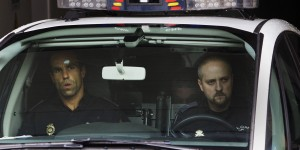 Police carry arrested train driver Francisco Jose Garzon Amo, center, partly seen in the back seat, to testify in court in Santiago de Compostela, Spain. (AP Photo/Lalo R. Villar)