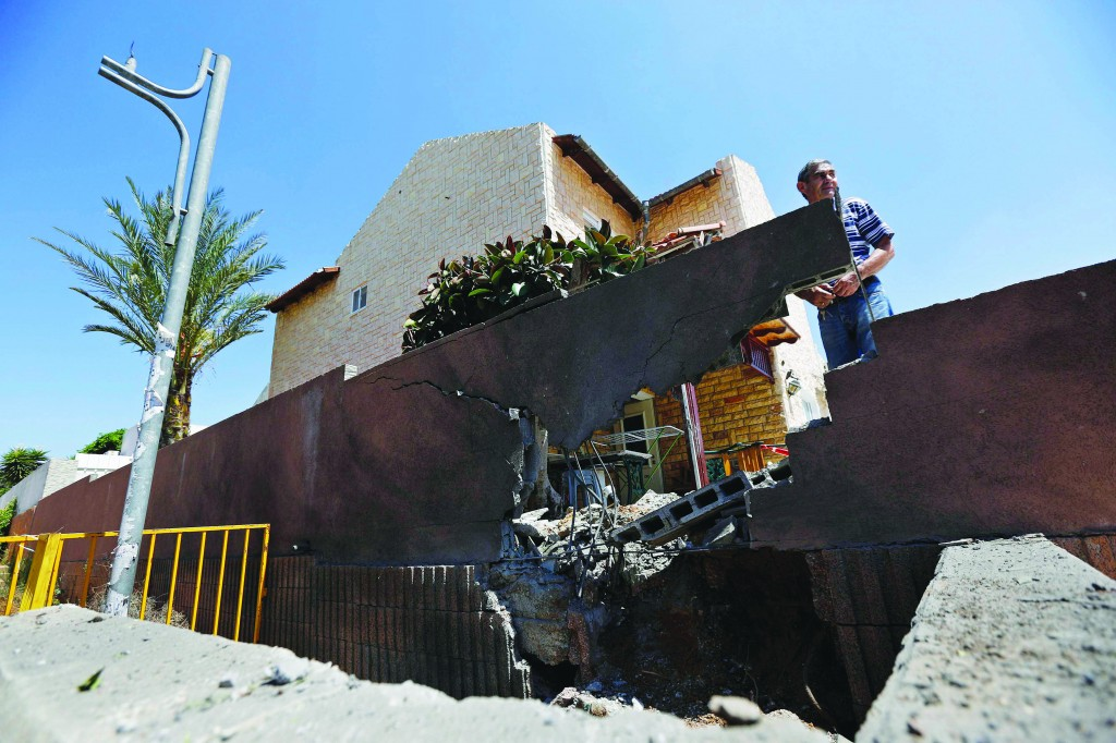 A homeowner stands next to the damaged wall surrounding his house after a rocket fired by Palestinian terrorists in Gaza landed in the southern town of Sderot, Thursday. (REUTERS/Amir Cohen)