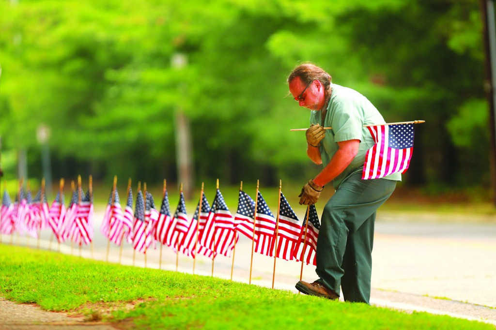 Groundskeeper Russ Price on Wednesday plants more than 100 U.S. flags at the entrance to the Red Bank Battlefield in National Park, N.J., in preparation for the Fourth of July. (AP Photo/The Philadelphia Inquirer, David Swanson)