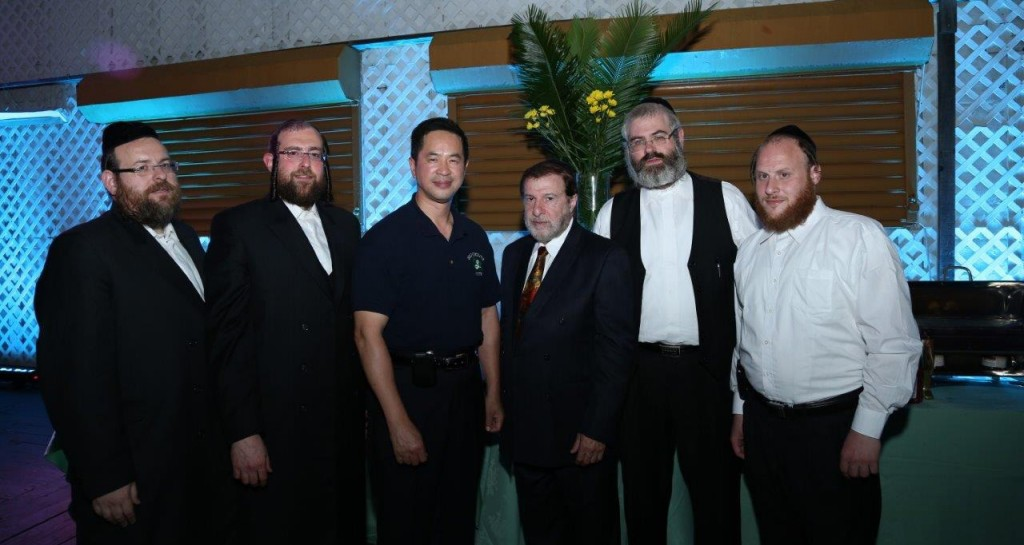 Thomas Chan, chief of the NYPD community affairs bureau (third left), with Shomrim head Simcha Bernath (second right) and Rabbi Abe Friedman, police chaplain (second left). (JDN)