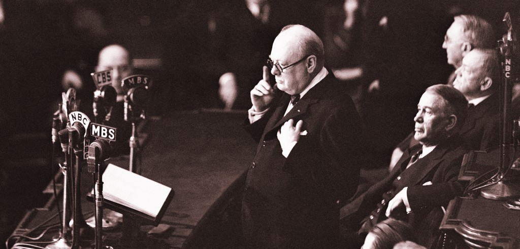 """With left hand over heart and his right forefinger pointed upward, British Prime Minister Winston Churchill stood on the green-carpeted Senate rostrum in Washington, D.C., on Dec. 26, 1941, and told members of the United States Congress in historic joint session, """"I believe in democracies."""" (AP Photo)"""