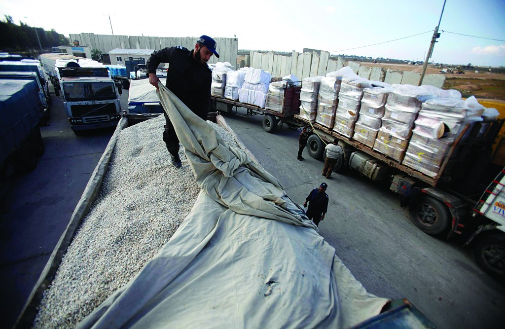 A Hamas agent checks a truck loaded with gravel at the Kerem Shalom crossing between Israel and the southern Gaza Strip, December 30. (REUTERS)