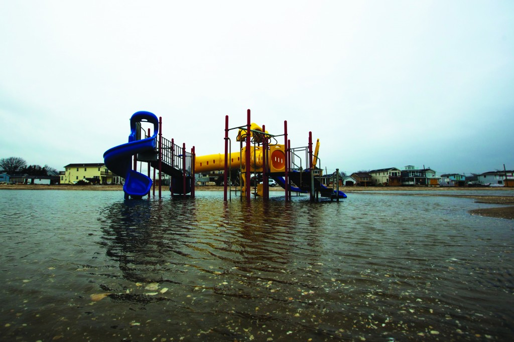 A playground stands in a large puddle of water between homes damaged two months ago by Superstorm Sandy and the ocean in the Queens borough region of Breezy Point, New York, this past Friday. (REUTERS/Lucas Jackson)