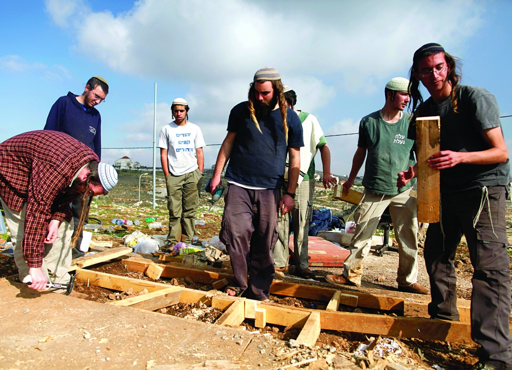 Local residents disassembling the outpost of Oz Tzion on Sunday after security forces carried out an evacuation. (FLASH90)