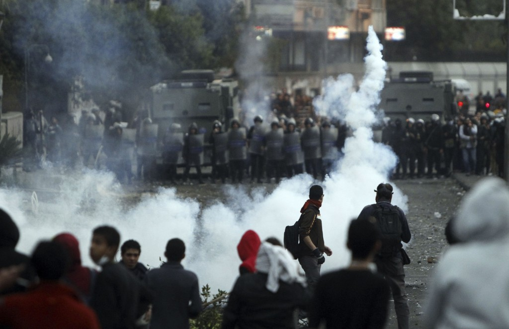 A protester opposing Egyptian President Mohamed Mursi throws a tear gas canister back at riot police during clashes along Qasr Al Nil bridge, which leads to Tahrir Square, in Cairo Tuesday. (REUTERS/Mohamed Abd El Ghany)