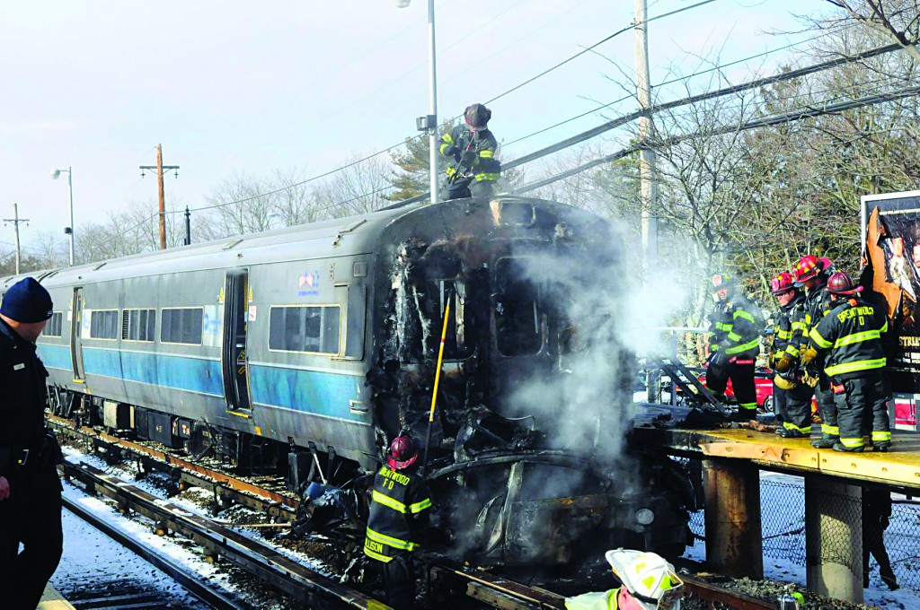 A car smolders after it was struck by an out-of-service Long Island Rail Road passenger train at the Brentwood Station Suffolk Avenue crossing on Tuesday morning. (AP Photo/Newsday, James Carbone)