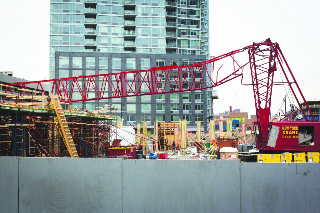 A mangled crane lies at the construction site in the Queens borough of New York where it collapsed, Wednesday. (AP Photo/John Minchillo)