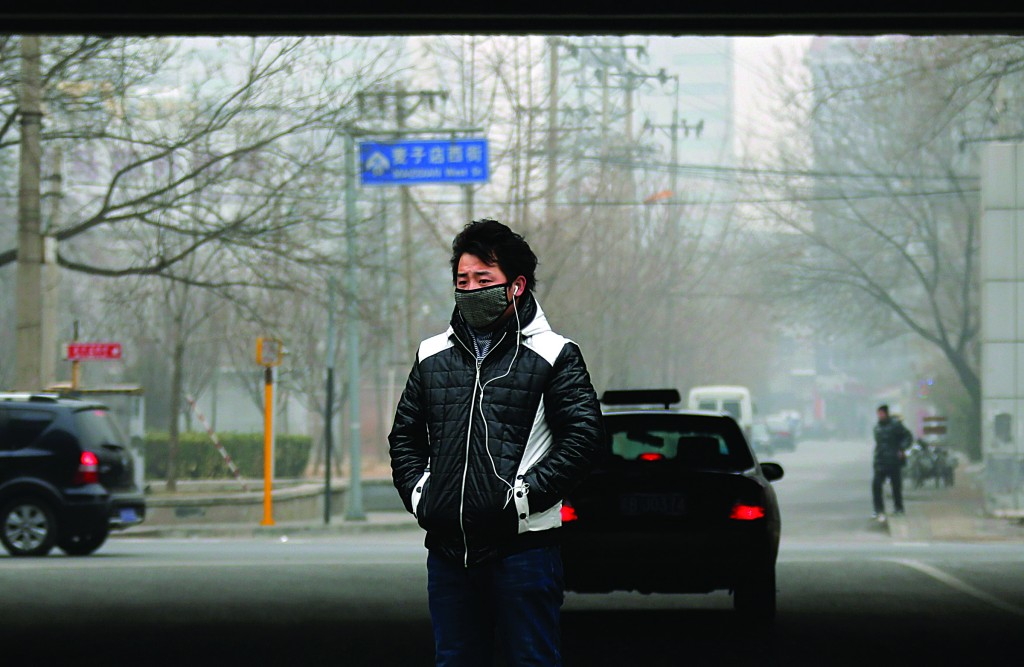 A man wearing a face mask stands on a street in central Beijing. (REUTERS/Petar Kujundzic)