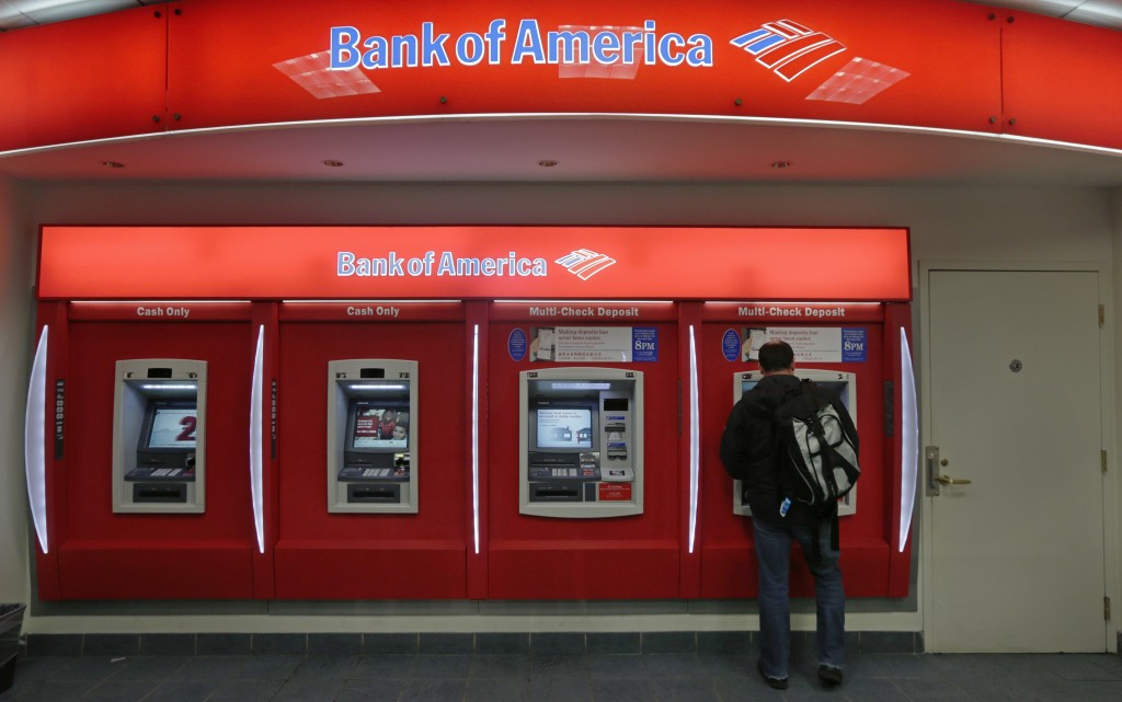 A customer stops at a Bank of America ATM office in Boston. Bank of America Corp. says it will spend more than $10 billion to settle mortgage claims resulting from the housing meltdown. (AP Photo/Charles Krupa)