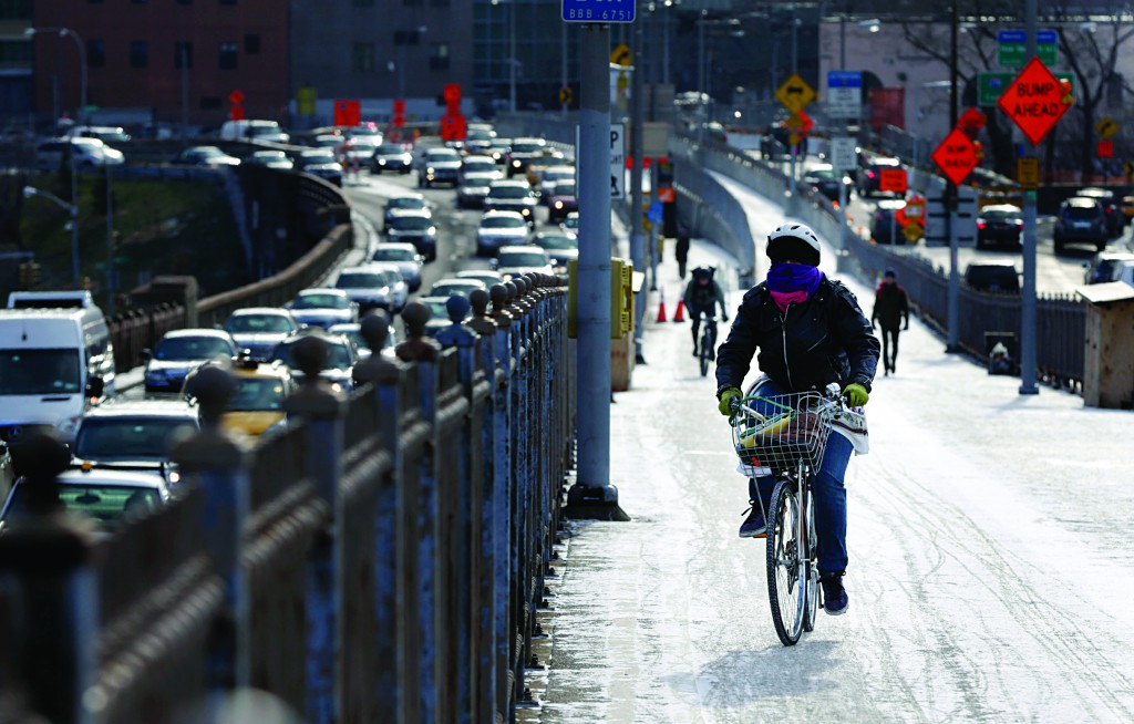 A dusting of snow greets a bundled up bicyclist on the Brooklyn Bridge in New York, Tuesday. Strong winds and frigid temperatures are expected in the New York area for the rest of the week. (AP Photo/Seth Wenig)