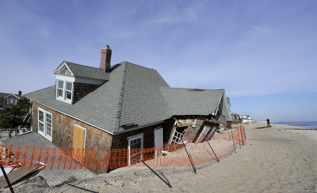A man photographs a beachfront home in Bay Head, N.J., that was severely damaged two months ago by Superstorm Sandy, Thursday. (AP Photo/Mel Evans)