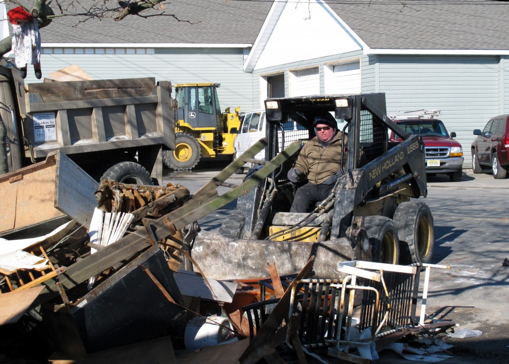 A worker uses a small front-end loader to remove Superstorm Sandy debris from the front of a home in Seaside Heights, N.J., on Monday. (APPhoto/Wayne Parry)