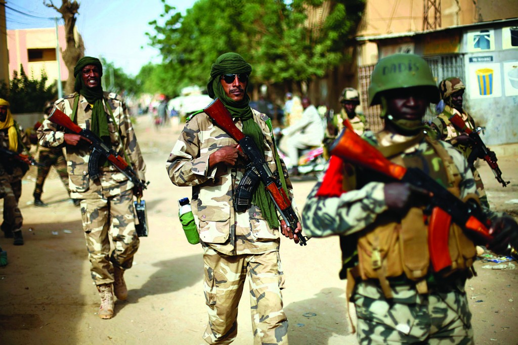 Chadian soldiers patrol the streets vacated by Islamic extremists in Gao, Northern Mali, Tuesday, days after Malian and French military forces closed in and retook the town from Islamist rebels. (AP Photo/Jerome Delay)