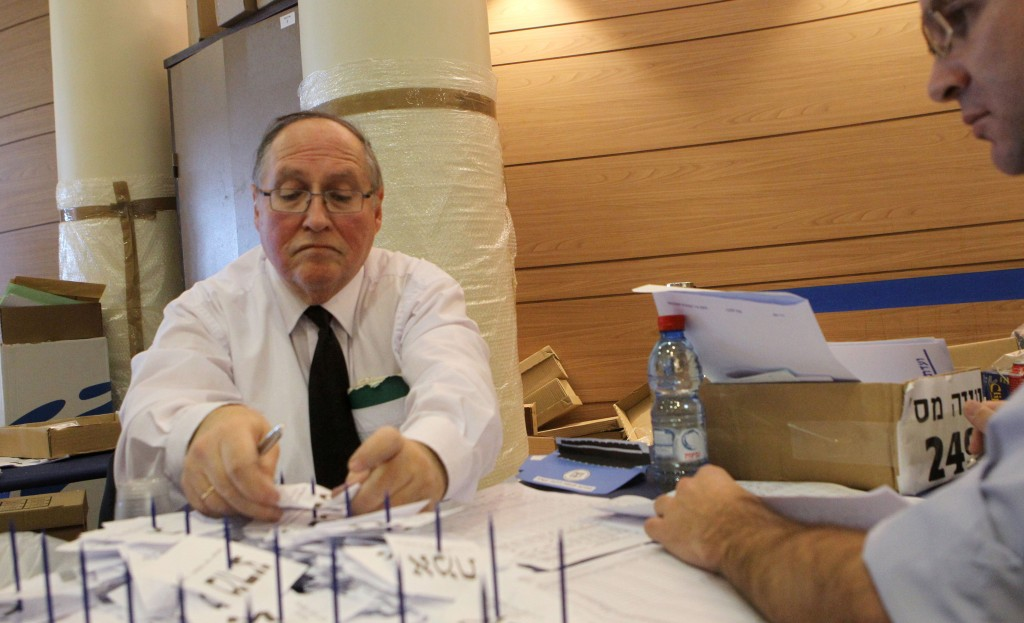 Elyakim Rubinstein, head of the Israeli Central Election Committee, counts the remaining ballots of soldiers and absentees at the Knesset on Thursday. (FLASH90)