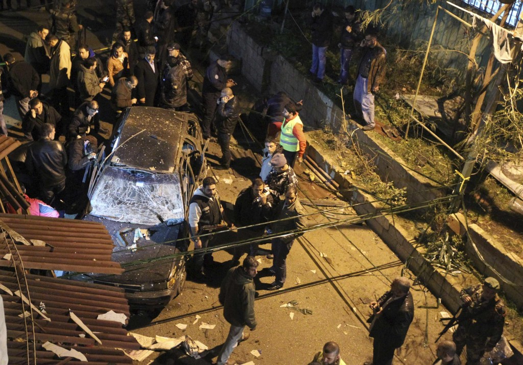 Security policemen inspect a damaged car in the suburbs of Beirut Monday. (REUTERS/Hassan Shaaban)
