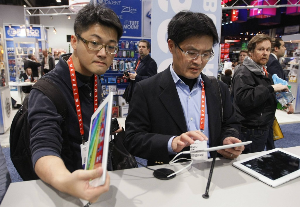 Showgoers check out Archos Android tablets at the Archos booth at the Consumer Electronics Show (CES) in Las Vegas. (REUTERS/Rick Wilking)