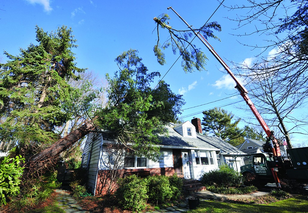 Sections of a tree are lifted by crane from the roof of a home by Green Mansion Tree Co. on Thursday, Sea Cliff, N.Y. The tree had fallen early this morning as a result of high winds. (AP Photo/Kathy Kmonicek)
