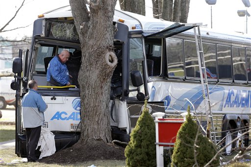 An investigator stands inside a commuter bus that crashed into a tree after colliding with a school bus Thursday, Jan. 10, 2013, in Old Bridge, N.J. The NYC-bound commuter bus and a mini-school bus crashed on a state highway in New Jersey, injuring at least 17 people, two critically. School officials said no students were on the Old Bridge school bus, which landed on its side along Route 9. (AP Photo/Mel Evans)