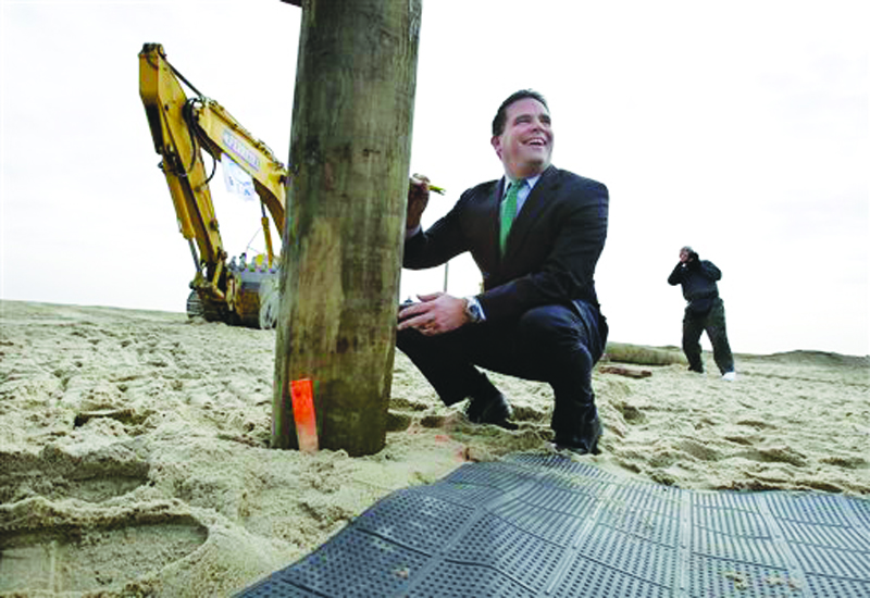 Belmar Mayor Matt Doherty signs the first piling of the new boardwalk construction Wednesday in Belmar, N.J. Belmar began construction on a 1.3-mile boardwalk to replace the walkway destroyed by Superstorm Sandy in October. The goal is to have it done by May. Doherty says a new design, including the use of strong hurricane tie-down straps, will help anchor the new boardwalk to its support moorings. The town intended to rebuild the boardwalk with tropical rain forest wood but abandoned those plans Tuesday, saying it wanted to avoid a protracted legal battle with environmentalists. (AP Photo/Mel Evans)