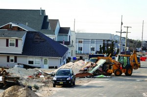 A worker uses a front loader to push debris and sand onto a mound near a damaged home as the cleanup process continues following Superstorm Sandy, Tuesday, in Seaside Heights, N.J. (AP Photo/Julio Cortez)
