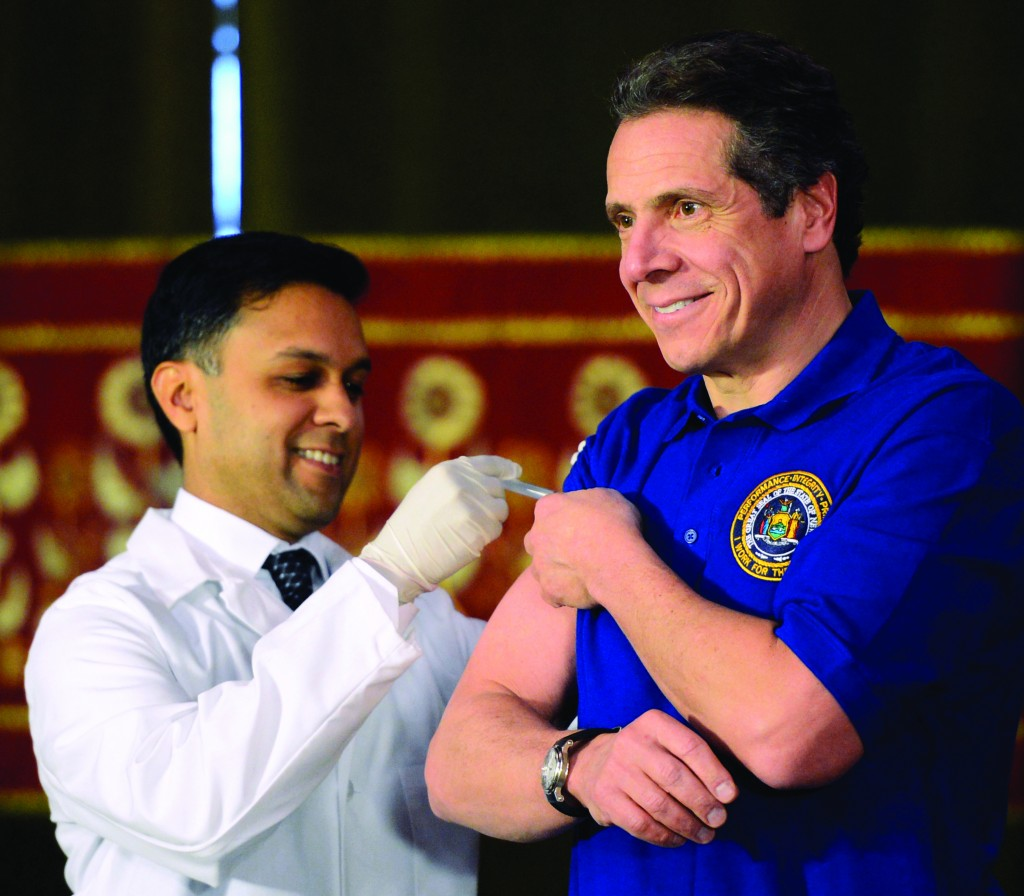 Gov. Andrew Cuomo (R) on Thursday gets a flu shot from DOH Commissioner Nirav Shah in the Red Room of the Capitol. (AP Photo/The Albany Times Union, Skip Dickstein)