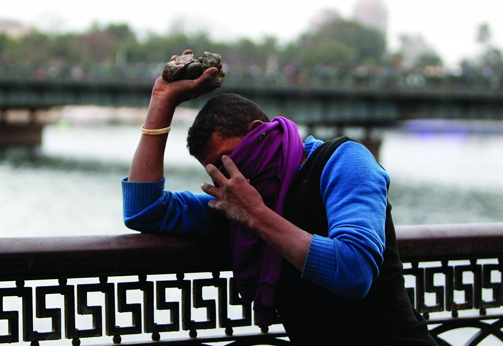 A protester opposing Egyptian President Mohamed Morsi covers his face during clashes along Qasr Al Nil bridge, which leads to Tahrir Square, in Cairo on Monday. (REUTERS/Mohamed Abd El Ghany)