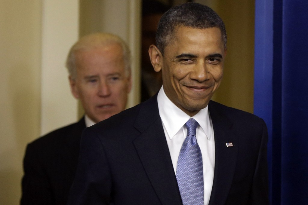President Obama smiles as he arrives with Vice President Joe Biden to make a statement regarding the passage of the fiscal cliff bill in the Brady Press Briefing Room at the White House in Washington, late Tuesday. (AP Photo/Charles Dharapak)