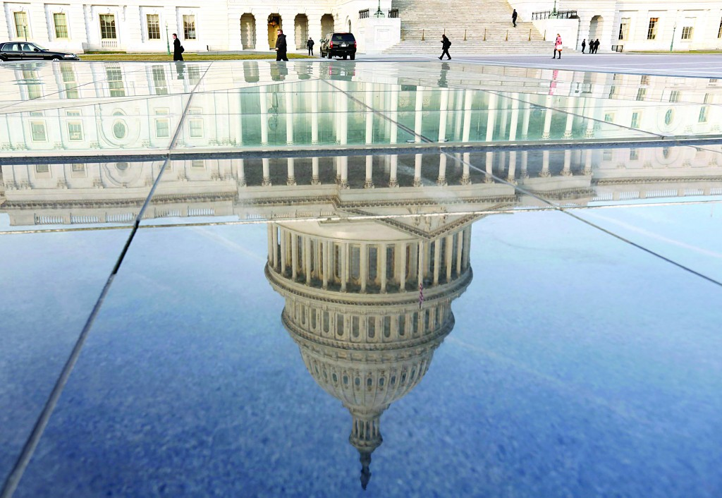The dome of the U.S. Capitol is reflected in a pool on the first day of the 113th Congress in Washington Thursday. (REUTERS/Kevin Lamarque)