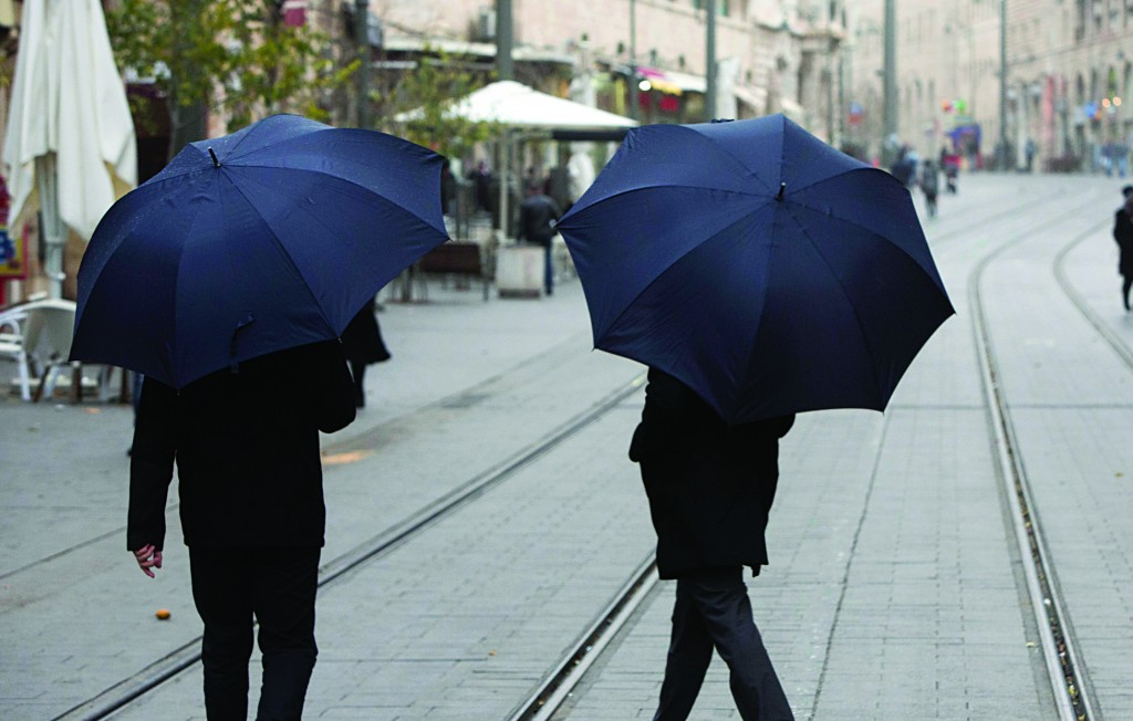 Israelis holding umbrellas as they walk on Jaffa Street in Yerushalayim as a major storm front moved in on Sunday. (Flash90)