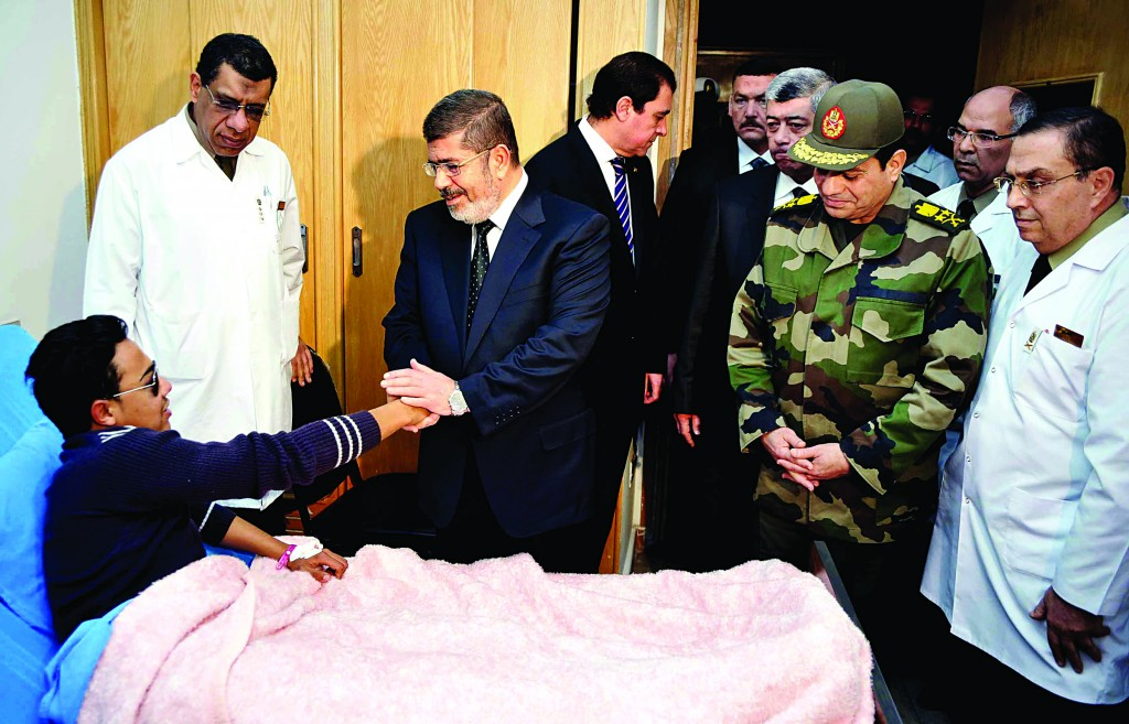 Egyptian President Mohammed Morsi, second left, visits yesterday a victim receiving treatment following a train crash south of Cairo at a military hospital. At least 19 people died and more than 100 were injured in the crash. (AP Photo/Egyptian Presidency)