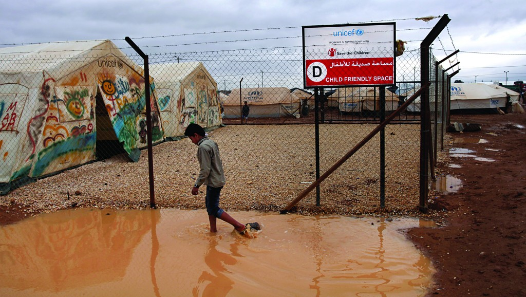 A Syrian refugee boy makes his way through water and mud, next to a UNICEF school at Zaatari Syrian refugee camp, near the Syrian border in Mafraq, Jordan, Tuesday. (AP Photo/Mohammad Hannon)