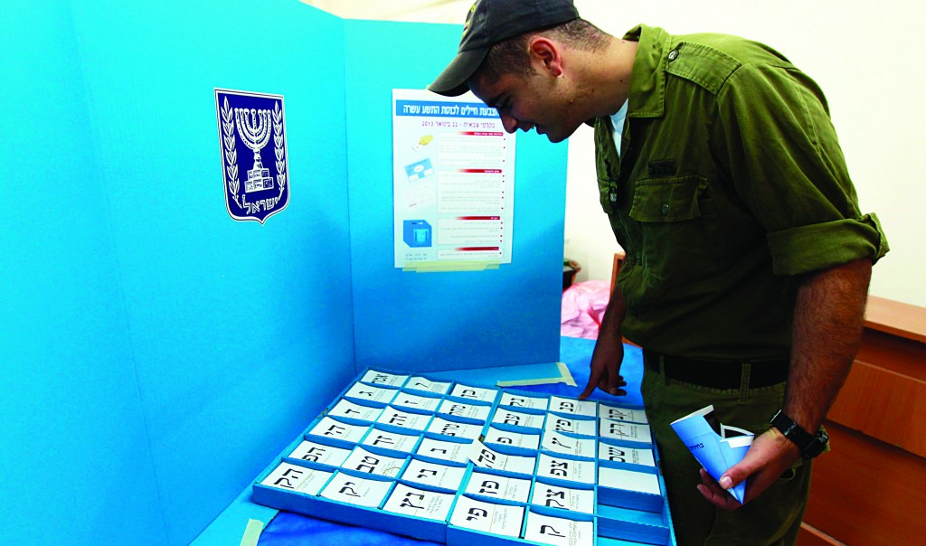 An Israeli soldier picks his ballot at a polling station in a navy base in Ashdod on Sunday. IDF soldiers started voting early. Polling stations for the rest of the country open on Tuesday. (REUTERS)