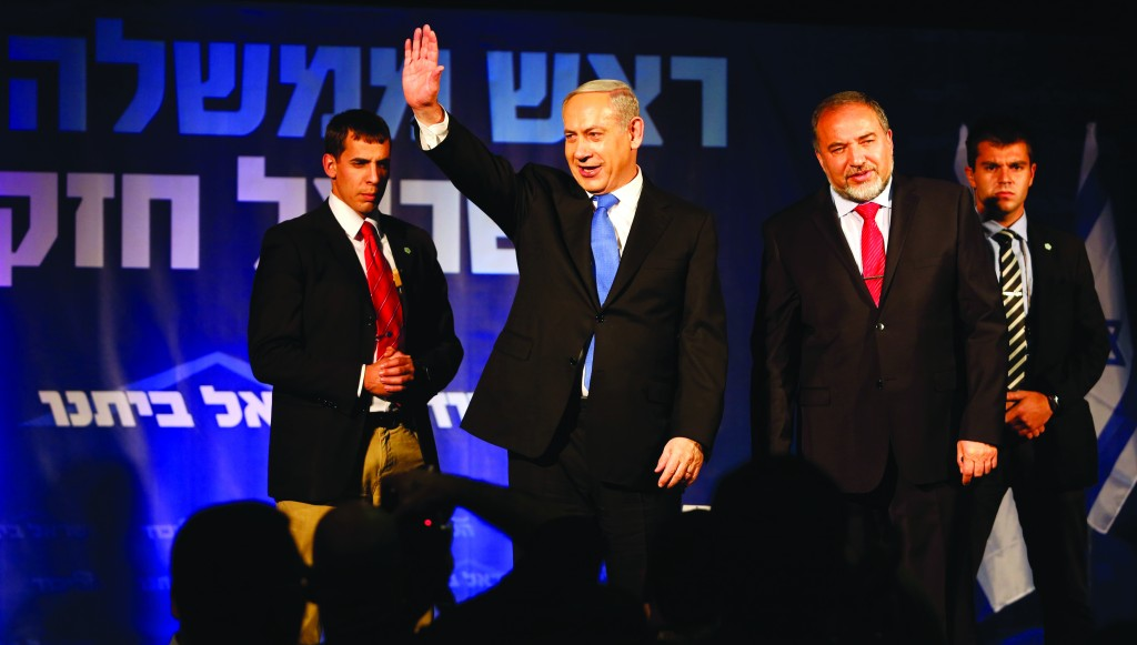 Israel's Prime Minister Binyamin Netanyahu yesterday waves as he stands next to former foreign minister Avigdor Lieberman at the Likud party headquarters in Tel Aviv. (REUTERS/Baz Ratner)