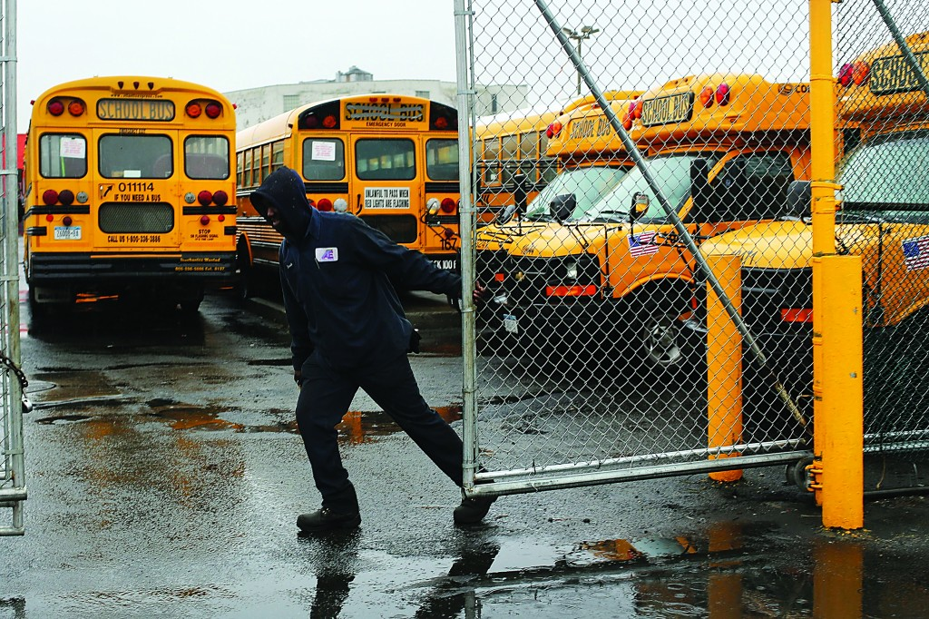 A worker with Atlantic Express closes the gate for school buses after more than 8,000 New York City school bus drivers and aides went on strike over job protection yesterday. The strike, the first since 1979 which lasted 14 weeks, left some 152,000 students, many with disabilities, without transportation to school. (Spencer Platt/Getty Images)