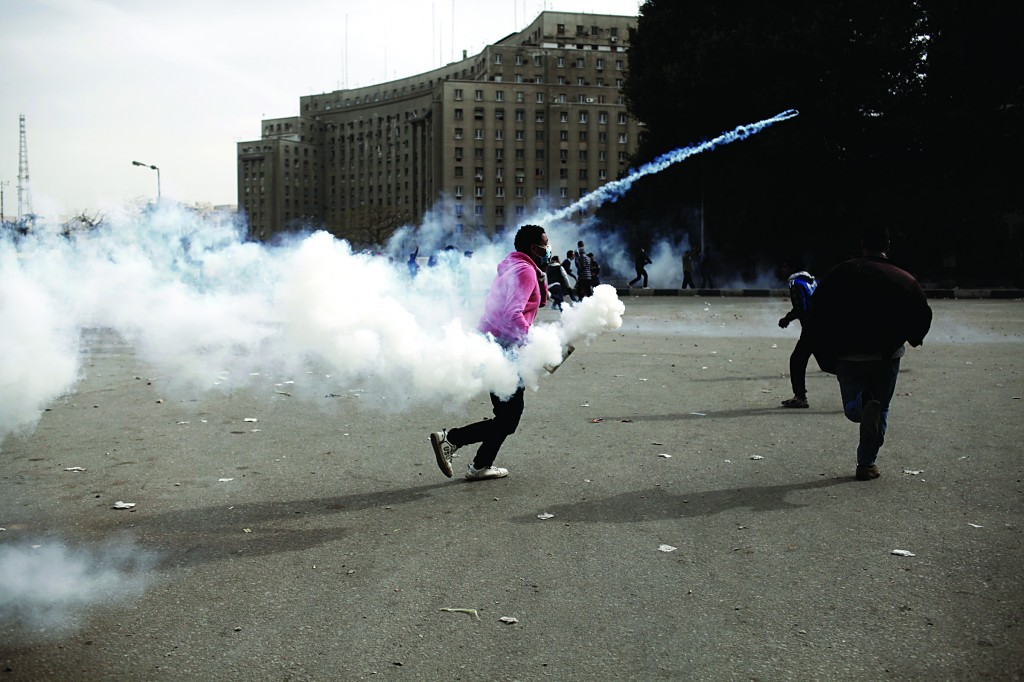An Egyptian protester throws a live tear-gas canister back towards riot police during a demonstration in Tahrir Square on Sunday in Cairo, Egypt. Egyptian President Mohammed Morsi declared a month-long state of emergency on Sunday in three cities along the Suez Canal which have been the focus of anti-government violence that has killed dozens. (Ed Giles/Getty Images)