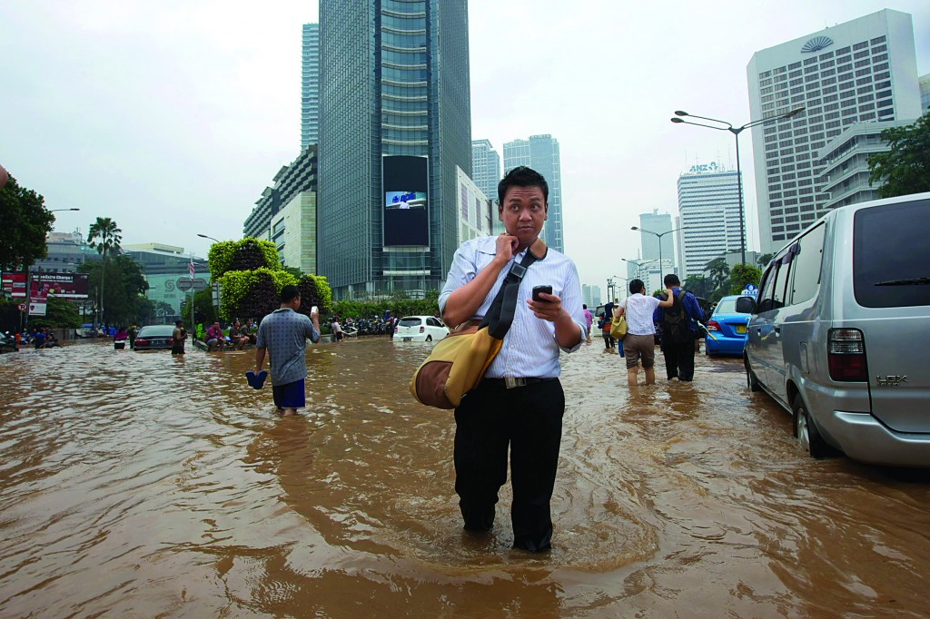 People wade through floodwaters in the central business district of Jakarta, Indonesia, on Thursday. Thousands of Indonesians were displaced and many key areas of the capital were covered in over a meter of water after days of heavy rain. (Ed Wray/Getty Images)