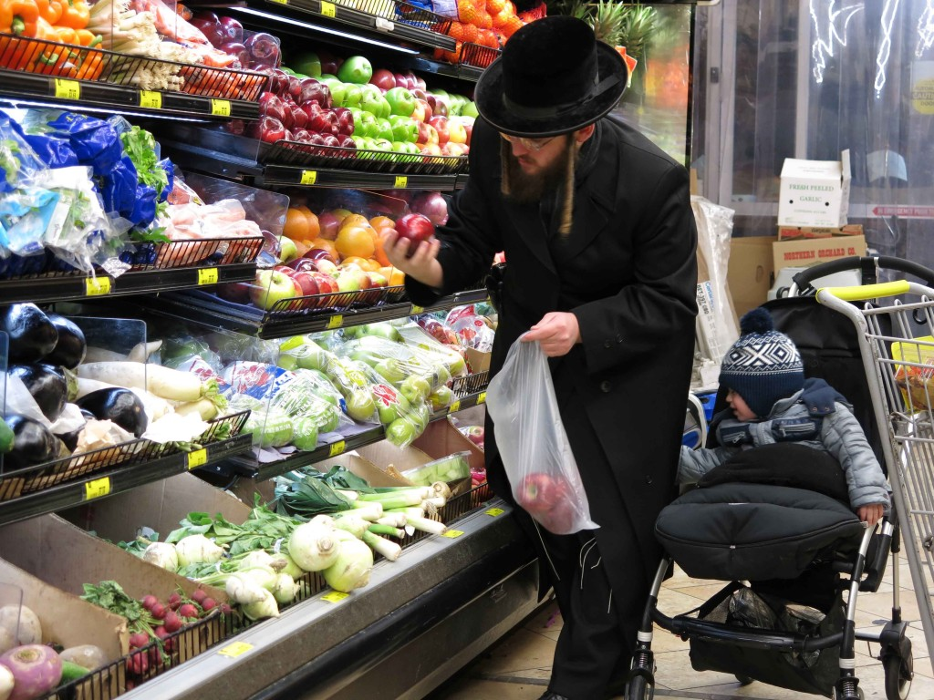 A father purchasing fruits in honor of Tu BiShvat at a local grocery in Boro Park. (Heshy Rubinstein Dee Voch)