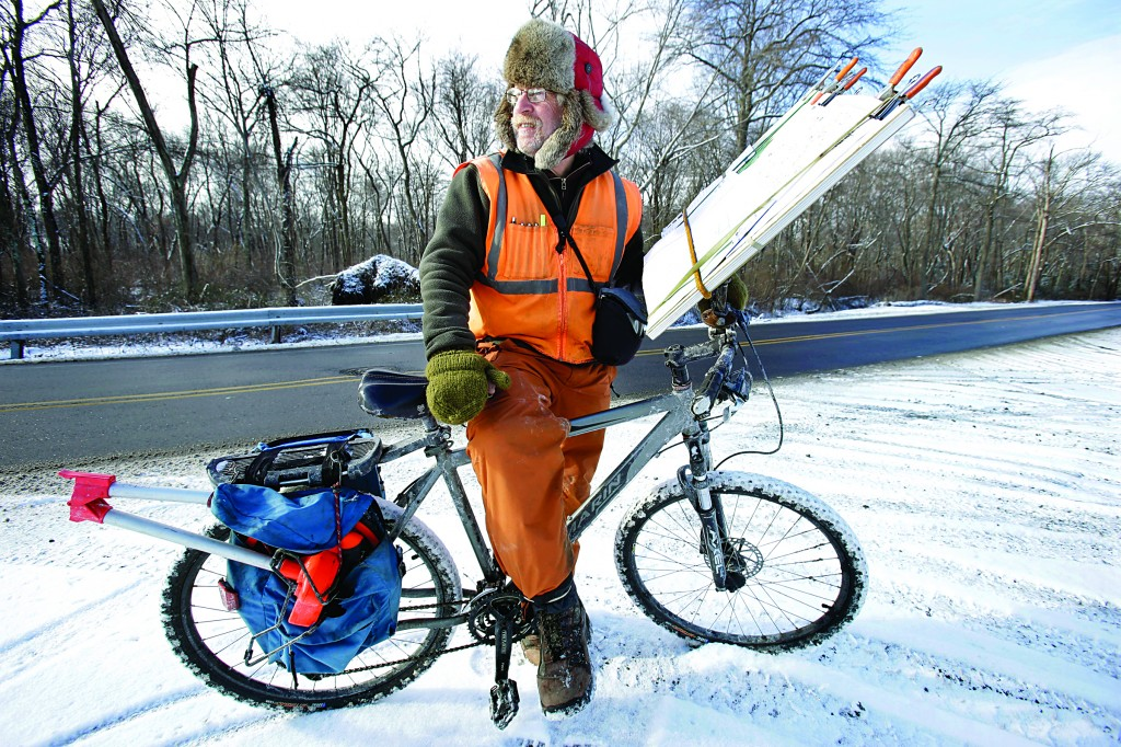 Brian Spatafora, of Portland, Maine, stops on the side of the road over the weekend in Hamilton, N.J., on his bicycle with a large chart that plots telephone poles that he must check. For months Spatafora has been riding his bike during the work day in New York and now New Jersey, checking thousands of poles for Optimum to use. (AP Photo/Mel Evans)