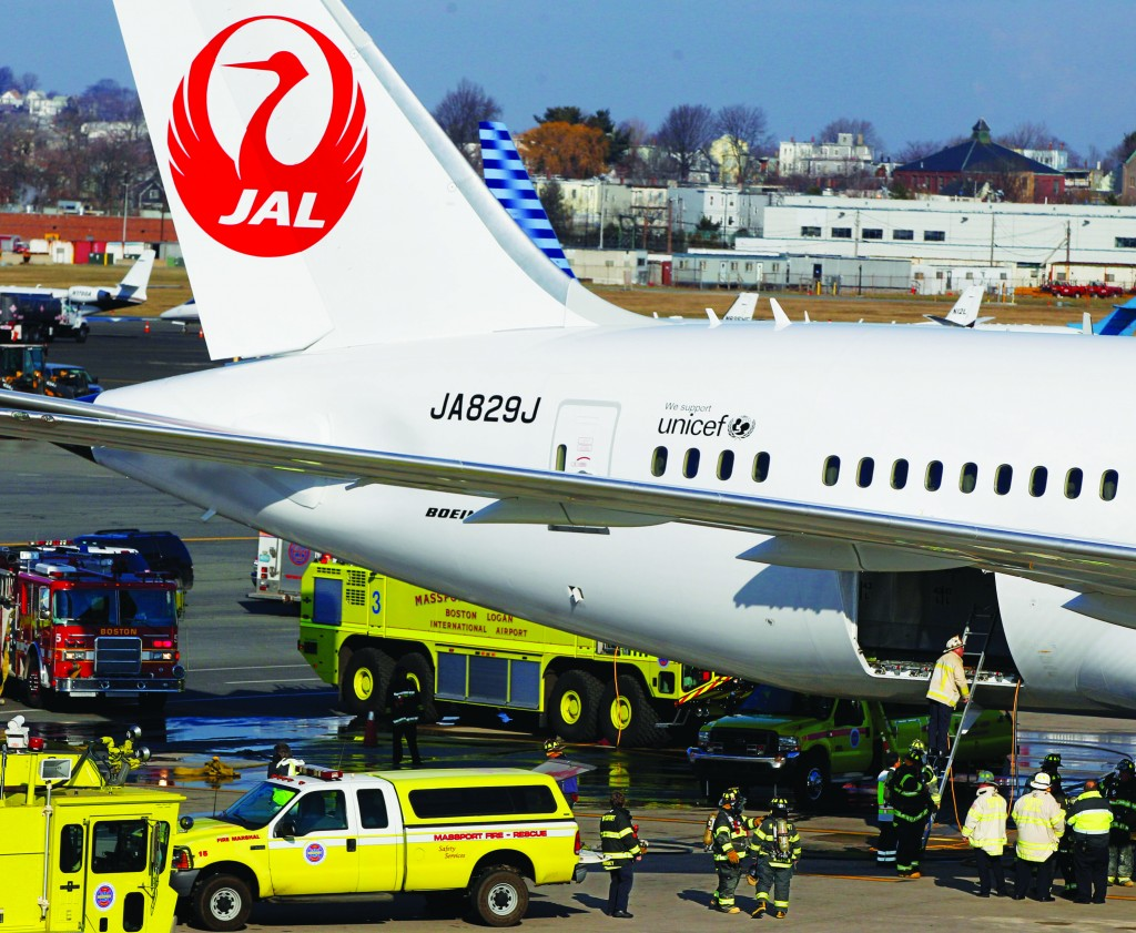 A Japan Airlines Boeing 787 Dreamliner jet aircraft is surrounded by emergency vehicles while parked at a terminal E gate at Logan International Airport in Boston as a fire chief looks into the cargo hold Monday. A small electrical fire filled the cabin of the JAL aircraft with smoke Monday morning about 15 minutes after it landed in Boston. (AP Photo/Stephan Savoia)