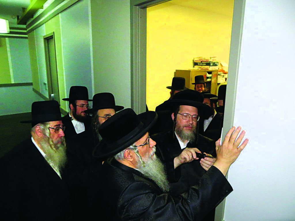 R-L: The Galanta Rebbe and the Dinover Rebbe affix a mezuzah at the new offices of the Rav Tov organization in Williamsburg. Rav Tov helps facilitate aid for Jews in Iran and similarly dangerous areas. Partially obscured is Rabbi Moshe Dovid Niederman, menahel of the organization and head of the UJO of Williamsburg. (JDN)