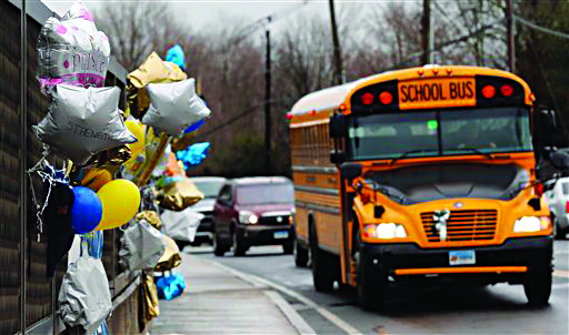 In this Dec. 18 photo, a school bus rolls toward a memorial in Newtown, Conn., for victims of the Sandy Hook Elementary School shooting. (AP Photo/Charles Krupa, File)