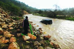 An Israeli man holds ropes as he stands near a car which was swept away during flash floods near Jerusalem yesterday. At least 17 people have died due to a winter storm in Lebanon, Jordan, Turkey, Israel and the Palestinian territories. Meteorological agencies in Israel and Lebanon both called it the worst storm in many years. (REUTERS)