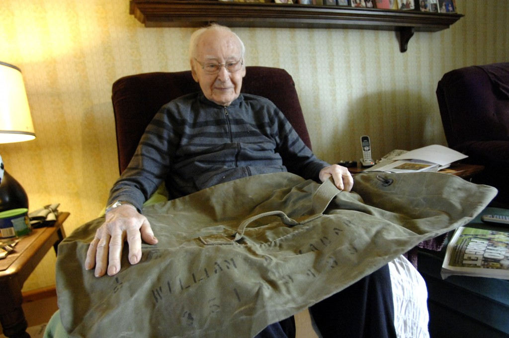 World War II veteran William Kadar holds his old Army duffel bag that bears his name at his home in Merrillville, Ind. The 92-year-old Kadar says he last saw the bag in November 1944, a month before he was captured by the Germans. His granddaughter says a 16-year-old French boy found the bag in his grandfather's house and tracked Kadar down. (AP Photo/Post-Tribune, Stephanie Dowell)